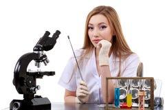 De mooie vrouwenwetenschapper in het laboratorium voert diverse handelingen uit Stock Afbeelding