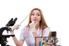 De mooie vrouwenwetenschapper in het laboratorium voert diverse handelingen uit Stock Afbeeldingen
