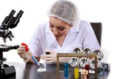 De mooie vrouwenwetenschapper in het laboratorium voert diverse handelingen uit Royalty-vrije Stock Foto's