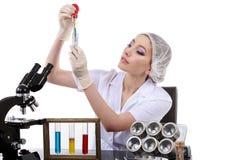De mooie vrouwenwetenschapper in het laboratorium voert diverse handelingen uit Stock Fotografie