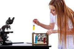 De mooie vrouwenwetenschapper in het laboratorium voert diverse handelingen uit Stock Foto