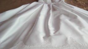 De mooie witte huwelijkskleding van de bruid ligt op een reusachtig bed stock videobeelden