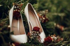 De mooie witte schoenen met rode boeketten op groen gras sluiten omhoog royalty-vrije stock fotografie