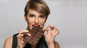 De mooie womanwith blauwe ogen en de rode lippen genieten van etend smakelijke melkchocola bij een fotostudio Stock Foto's