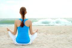 De mooie yoga van de vrouwenpraktijk op het strand Stock Afbeelding