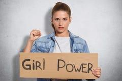 De mooie zekere jonge vrouw met ernstige uitdrukking, toont vuist, demonstares haar macht, behoort tot feministe, draagt denim ja royalty-vrije stock foto's