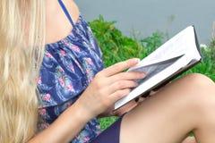 De mooie zitting van de blonde jonge vrouw op het gras en lezing een boek Close-up, vrouwelijke benen royalty-vrije stock afbeelding