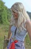 De mooie zitting van de blonde haired jonge vrouw in openlucht Stock Afbeeldingen