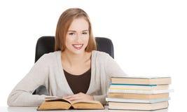 De mooie zitting van de studentenvrouw door het bureau met boeken en leert Stock Afbeelding