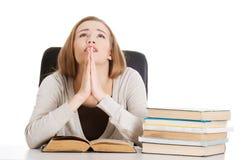 De mooie zitting van de studentenvrouw en het bidden met stapel boeken. Stock Afbeelding