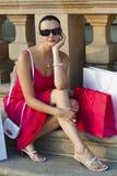 De mooie Zitting van de Vrouw met het Winkelen Zakken stock afbeeldingen
