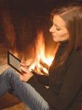 De mooie zitting van de vrouwenlezing ebook dichtbij de haard royalty-vrije stock afbeelding