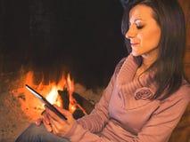 De mooie zitting van de vrouwenlezing ebook dichtbij de haard stock foto
