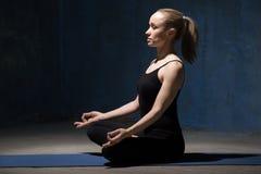 De mooie zitting van de Yogavrouw op meditatiezitting Stock Afbeelding