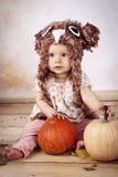 De mooie zitting van het babymeisje met pompoenen die gebreide hoed dragen Stock Afbeeldingen