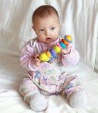 De mooie zitting van het babymeisje met stuk speelgoed Stock Afbeelding