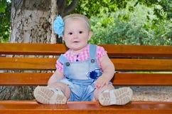De mooie zitting van het babymeisje op de bank Royalty-vrije Stock Foto's