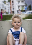 De mooie Zitting van het Babymeisje op de Concrete Bank Royalty-vrije Stock Afbeeldingen