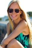 De mooie zitting van het blondemeisje op het dak Stock Afbeelding