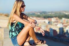 De mooie zitting van het blondemeisje op het dak Royalty-vrije Stock Afbeelding