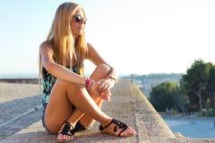 De mooie zitting van het blondemeisje op het dak Stock Foto