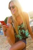 De mooie zitting van het blondemeisje op het dak met mobiele telefoon Stock Fotografie