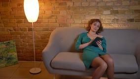 De mooie zitting van het gember krullend-haired Kaukasische meisje op bank en het letten op in tablet ernstig en tiredly op comfo stock video