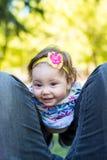 De mooie zitting van het jong geitjemeisje op vaderbenen in openlucht royalty-vrije stock fotografie