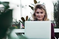 De mooie zitting van het studentenmeisje op een bank met laptop en het doen van het werk aangaande freelance concept het droomwer royalty-vrije stock foto's