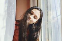 De mooie zitting van het tienermeisje door het venster royalty-vrije stock foto