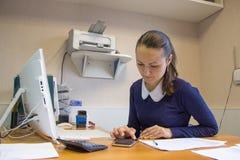 De mooie zitting van de meisjesbeambte bij werkplaats dichtbijgelegen monitor Stock Afbeeldingen