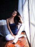 De mooie zitting van de vrouwenballerina op vloer in het ochtendzonlicht stock foto