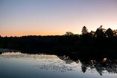 De mooie zonsondergang van de de recente zomernacht met kalme waterbezinningen en donkere bomen tegen duidelijke hemel stock fotografie