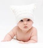 De baby in witte hoed ligt op bed Stock Fotografie