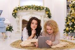 De mooie zusters lachen en met hulp van gadget en betaalpaspa Stock Foto's