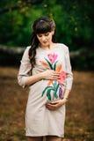 De mooie zwangere vrouw bevindt zich en kijkt mooi op buik Royalty-vrije Stock Foto's