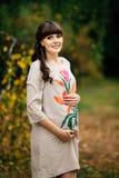 De mooie zwangere vrouw bevindt zich mooi op het gele gazon Stock Afbeelding