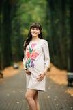 De mooie zwangere vrouw bevindt zich mooi op het gele gazon Stock Foto's
