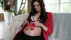 De mooie zwangere vrouw in bustehouder en rood jasje houdt leuke rode babyschoenen, bekijkt camera en glimlacht terwijl stock videobeelden