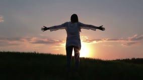 De mooie zwangere vrouw heft haar handen aan de zon op bij zonsondergang stock video