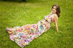 De mooie zwangere vrouw ligt op een groen gazon Stock Afbeeldingen