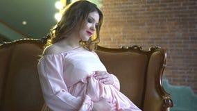 De mooie zwangere vrouw met samenstelling in een elegante roze kleding zit thuis op de laag stock videobeelden