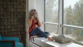De mooie zwangere vrouw in rood overhemd en zwarte bustehouder zit op de vensterbank dichtbij de de muur en het drinken thee stock video