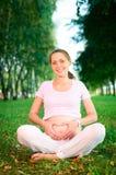 De mooie zwangere vrouw toont een hart Royalty-vrije Stock Foto
