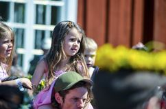 De mooie Zweedse mensen en dissapointed jonge geitjes genieten van traditionele decoratie die van medio de zomerdag kleurrijke kr stock fotografie