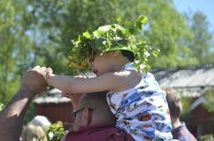 De mooie Zweedse mensen en de jonge geitjes genieten van traditionele decoratie die van medio de zomerdag kroon dragen die van bl stock fotografie