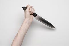 De moord en Halloween als thema hebben: Een man hand die voor een mes, een menselijke hand bereiken die een mes houden die op een royalty-vrije stock afbeelding