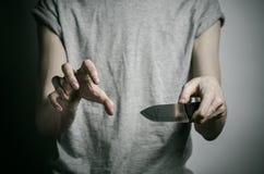 De moord en Halloween als thema hebben: een mens die een mes op een grijze achtergrond houden stock afbeelding
