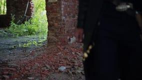 De moordenaar in een zwarte mantel en een hoed gaat het grondgebied van een verlaten fabriek in stock footage