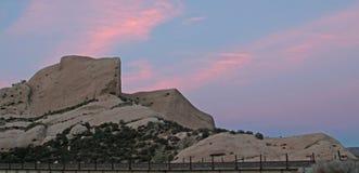 De mormoonse Rotsen voor spoorwegsporen onder roze zonsondergangwolken in hoog Californië verlaten enkel buiten San Bernardino royalty-vrije stock fotografie